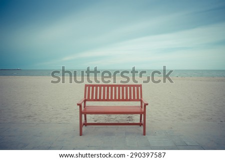 Alone wooden red beach chair sitting on the sand with sea.vintage color - stock photo