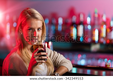 Alone young girl sitting at bar desk. - stock photo