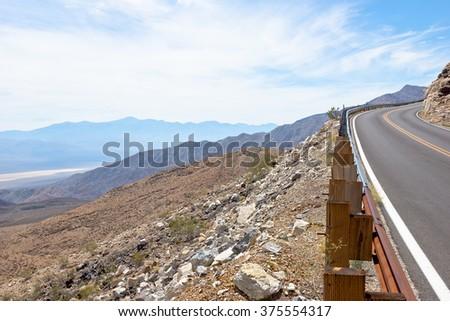 Along a hillside a desert road runs up hill.  - stock photo
