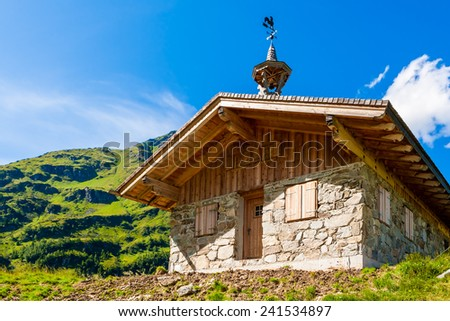 Alpen house with mountain, green grass and blue sky with clouds on background. - stock photo