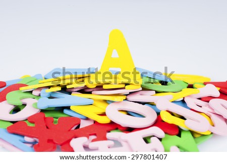 Alphabet A on the top of the hill of pile other alphabet with red, yellow, green, pink and blue colour, education and leading concept, selective focus - stock photo