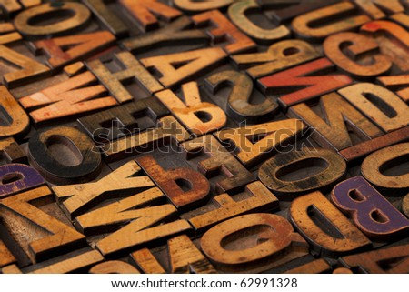 alphabet abstract - vintage wooden letterpress types, stained by color inks, selective focus - stock photo
