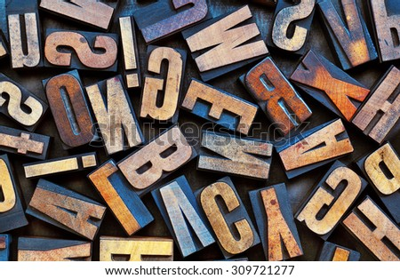 alphabet background - vintage letterpress wood printing blocks placed randomly on a grunge metal tray - stock photo