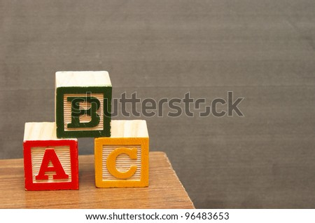 Alphabet blocks in front of the chalkboard for learning the basics of the english language. - stock photo