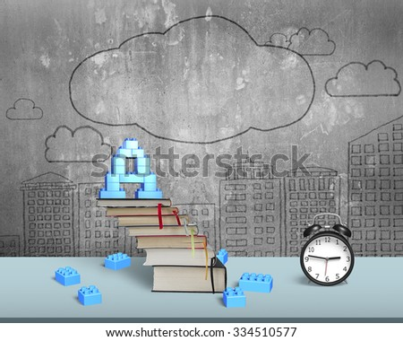 Alphabet letter A shape blocks on top of stack books stairs with alarm clock on table, with doodles concrete wall background. - stock photo