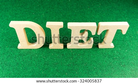 Alphabet letter DIET wooden block on green grass carpet. Concept of dieting. Isolated over the white background. Slightly defocused and close up shot. Copy space. - stock photo