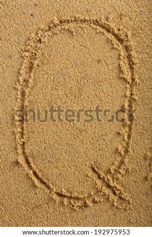 Alphabet letter written on wet beach sand - stock photo