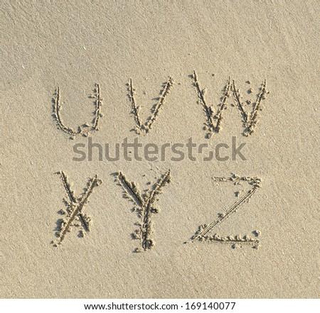 alphabet letters handwritten in sand on beach - stock photo