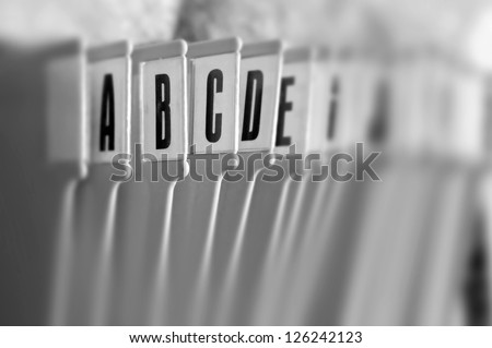 Alphabetical filing tray office index organizer. Selective focus black and white. - stock photo
