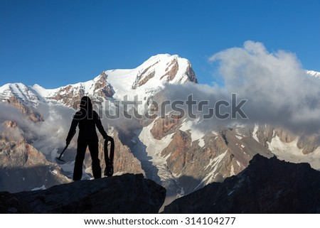 Alpine Climber Arranging Descent with Rope and Ice Axe  Silhouette Woman Staying on Top of Rock Cliff Holding Climbing Gear Stormy Clouds and Peaks Illuminated bright Morning Sun - stock photo