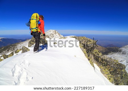 Alpine climber arrived on the summit during winter climb - stock photo