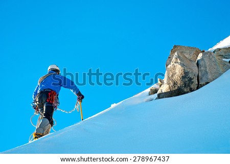 Alpine climber balances on the ice snowfield - stock photo