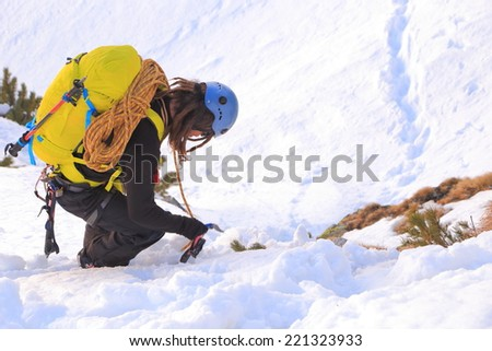 Alpine climber carries the rope on backpack on snowy terrain - stock photo