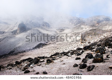Alpine desert - arid and barren - shrouded in clouds with the blue sky beyond peaking through. Taken on the slopes of Mt kilimanjaro, Tanzania - stock photo
