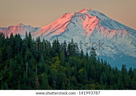 Alpine Glow Viewed from Castle Crags State Park, warm sunset light illuminates the western face of Mount Shasta, Cascade Range, California. - stock photo
