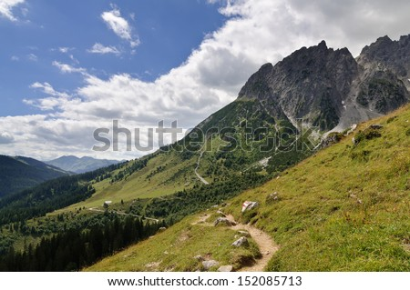 alpine hiking trail with trail marker leading through meadow, view of Taghaube and the pasture of Stegmoosalm, mountain Hochkoenig, Salzburg, Austria - stock photo