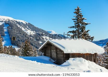 Alpine landscape. Snow-covered house, ski lift chairs, mountains. Tyrol, Austria - stock photo