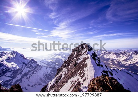Alpine landscape with peaks covered by snow  - stock photo