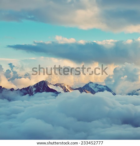 alpine landscape with peaks covered by snow and clouds. natural mountain background. vintage stylization - stock photo