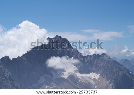Alpine mountains, the peak is covering by clouds - stock photo