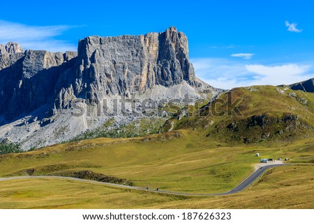 Alpine road and parking in mountain valley near Passo Giau, Dolomites Mountains, Italy  - stock photo