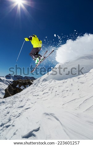 Alpine skier skiing downhill, blue sky on background - stock photo