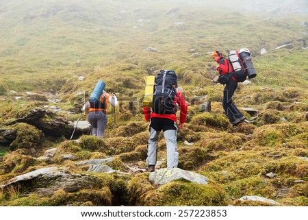Alpine trekking - harsh foggy conditions - stock photo