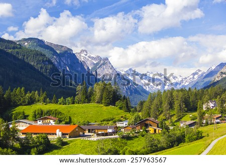 Alpine village under Innsbruck in Austria in the green valley among the mountains - stock photo