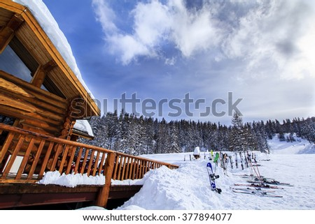 Alpine wood lodge with a lot of ski and snowboards left in front of it. Wide-angle lens - stock photo