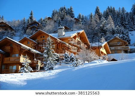 Alpine wooden chalet in the sunny mountains in winter, Meribel, Three Valleys, France - stock photo
