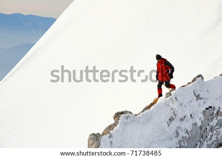 Alpinist descending an icy mountain slope - stock photo