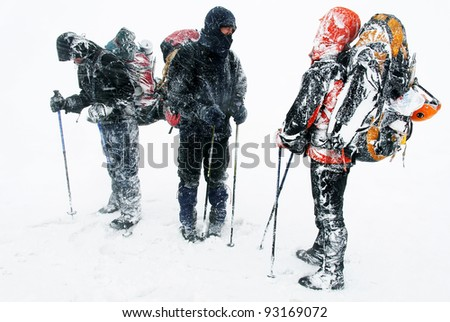 Alpinists facing a harsh blizzard - stock photo