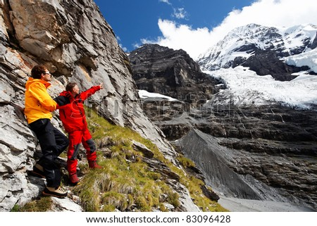 Alpinists pointing a mountain route on Monch Peak (4107m), Berner Oberland, Switzerland - stock photo