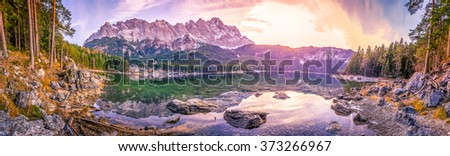 Alps mountains reflected in a lake at sunset - Panoramic view with the bavarian Alps mountains mirrored in the water of the Eibsee lake, located in Grainau, Germany, at dusk. - stock photo