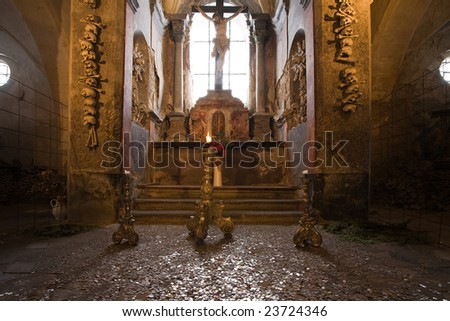 Altar in old church ossuary with human skulls and bones on walls, Kutna Hora, Czech Republic. - stock photo