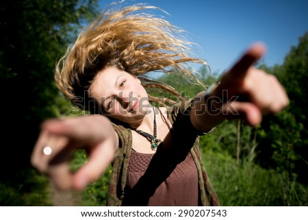 Alternative beautiful girl whipping her hair sideways while pointing fingers outward - stock photo
