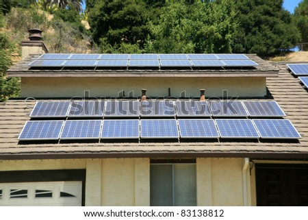 alternative energy photovoltaic solar panels on the roof of a home. collecting energy from the sun and helping save the earth from global warming and reducing their electric bills at the same time - stock photo