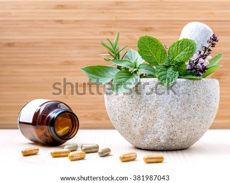 Alternative health care fresh herbs basil ,sage ,rosemary, mint  and herbal capsule with mortar on wooden background. - stock photo