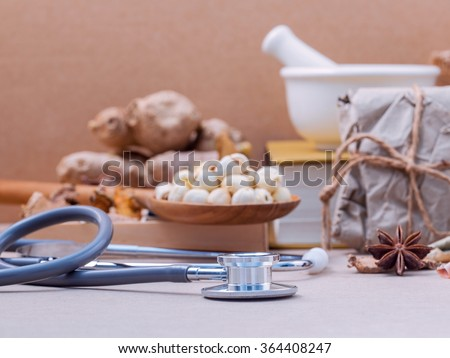 Alternative health care lotus seed in wooden spoon put on dried various Chinese herbs in wooden box and medical textbook with mortar on brown background. Depth of field selective focus on stethoscope. - stock photo