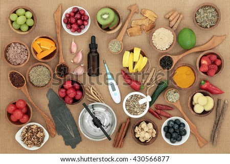 Alternative medicine and food selection for cold remedy with acupuncture needles, moxa sticks and thermometer over ridged brown paper background. - stock photo