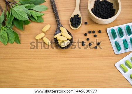 Alternative medicine, herbal pills, tablets , blisters of capsules  on wood background. - stock photo