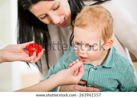 Alternative Medicine - Homeopathy.Young woman and her child at the doctor homeopaths. Treatment with herbs. Doctor gives homeopathic pills to child. Selective focus - stock photo