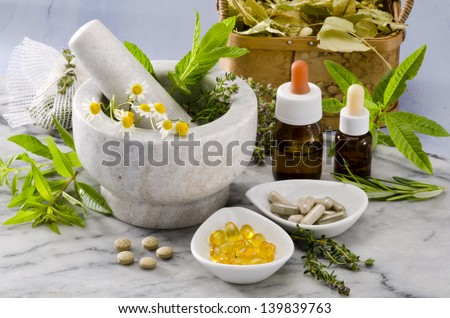 Alternative Medicine. Rosemary, mint, chamomille, thyme in a marble mortar. Essential oils and herbal supplements. - stock photo