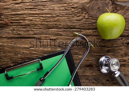 Alternative medicine - stethoscope, clipboard and green apple on wood table top view . Medical background. Concept for diet, healthcare, nutrition or medical insurance - stock photo