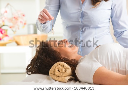 Alternative medicine therapist using pendulum to make a diagnosis - stock photo