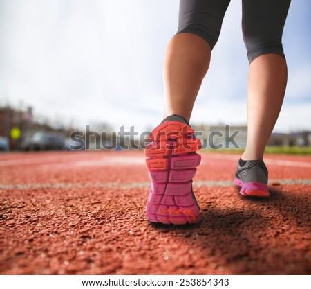 alternative perspective of woman running on a track mid-stride with a drama filter (shallow depth of field) - stock photo