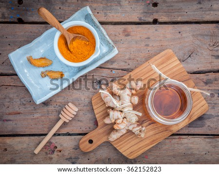 Alternative skin care - Homemade scrubs curcumin powder,honey and curcumin roots set up on old wooden table. - stock photo