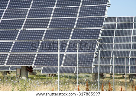 Alternative sources of producing electricity - PV meadow against the blue sky Concept for environmental protection - stock photo