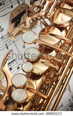 Alto Saxophone keys closeup with score notes in background - stock photo