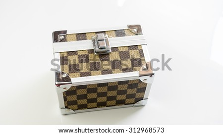 Aluminium metal checker box make up case or jewellery accessories box on empty background. Slightly de-focused and close-up shot. Copy space. - stock photo